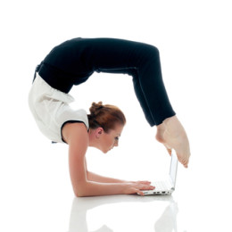 Businesswoman doing yoga and typing on netbook